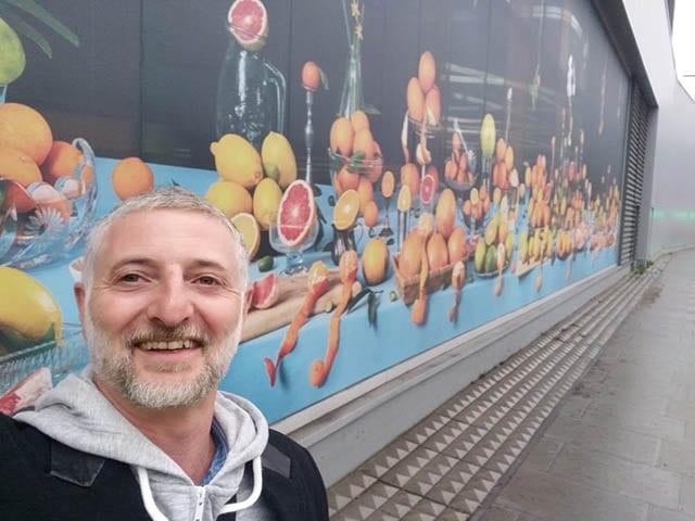 מגזין אופנה, צילום, איל גרניט ליד יצירתו 'טבע דומם פירות הדר'. צילום: יח״צ